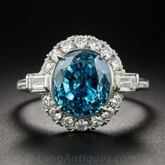 Vintage Zircon and Diamond Ring in Platinum. Handcrafted in platinum, circa 1940's -50's, a vibrant deep Caribbean blue, faceted oval zircon, weighing 5.7 carats, radiates from within a sparkling white halo of round brilliant-cut diamonds, punctuated by a horizontal set baguette diamond on each shoulder. The shank is adorned with a tiny beaded texture outlined by microscopic milgraining. | via langantiques.com