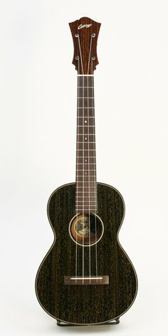 """This is a rare, Collings tenor uke in """"doghair"""" finish with tortoise binding and rope purfling. The instrument is all, solid mahogany and equipped with violin style, """"peghead"""" tuners. This is as fine a sounding and playing ukulele as anyone could ever ask for. 1-3/8"""" nut width"""