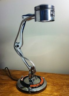 HD piston halogen light connected on two shifter arms wrapped by a stainless steel line. It stands on a Harley-Davidson derby cover with a screaming eagle emblem. A push switch fires it up.