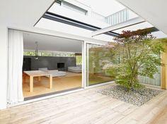 Wohnzimmer mit Schiebewände aus Glas auf die Veranda führend
