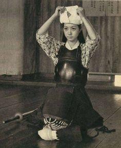 Female kendoka putting on tenugui before keiko