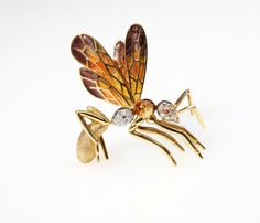 Lot# 1178 An Italian 18K yellow gold, enamel and diamond wasp brooch. , the wings enhanced with yellow, orange and violet enamel, the body set with 15 single-cut round diamonds, and one ruby eye, 2'' x 2'', 22 gms, est: $700/1000 *Price Realized: $1,800.00