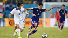 Japan's Kagawa attempts to hold off Greece's Georgios Karagounis.