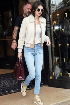 Kendall Jenner in a fuzzy cream bomber jacket over a white tee and skinny jeans