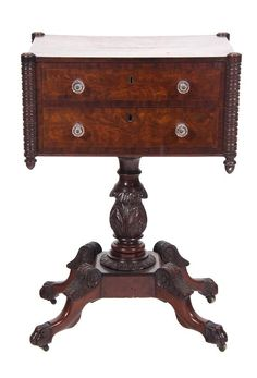 An American Empire Carved Mahogany Work Table  19th century  having a rectangular top, out set turned supports ending in acorn pendants flank two drawers with molded glass pulls, raised on ring and acanthus carved pedestal ending in four down curved legs headed by acanthus leaves, ending in paw feet on casters.  Height 30 x width 20 1/2 x depth 15 inches.