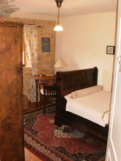 De nostalgische eenpersoonskamer met schrijftafel, confortabele fauteuil en grote kledingskast.