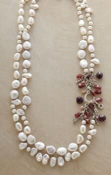 A double strand pearl necklace that adds excitement to a classic design with a splash of deep red gems.