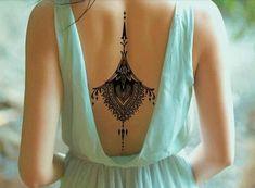 tattoo motive rücken mit schwarzem tattoo dekorieren frau mit schönem blauen kleid offener rücken