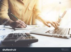 Close up of businesswoman or accountant hand holding pen working on calculator to calculate business data, accountancy document and laptop computer at office, business finance concept