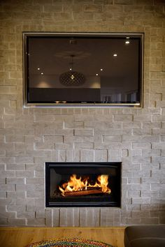 Exposed brick feature wall around the gas fireplace and TV offers adds texture to the family room. #exposedbrick #tvwall #indoorfireplace #fireplace #brodieretallick #house #generationhomes