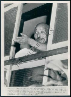 September 11, 1945. Hideki Tojo, former Japanese premier, gestures from his bungalow window to army officers who have come to take him into custody. A few seconds later he shot himself.