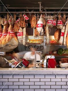 Meat and sausage hanging on butcher's hooks above tiled counter in English shop