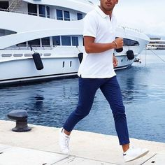 Consider pairing a white polo with blue trousers for a casual level of dress. Tap into some David Gandy dapperness and complete your look with white low top sneakers.   Shop this look on Lookastic: https://lookastic.com/men/looks/white-polo-blue-chinos-white-low-top-sneakers/21096   — White Polo  — Blue Chinos  — White Low Top Sneakers