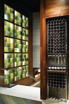 Empty wine bottles backlit by LED fixtures form a sculptural feature wall. LOVEEEEEEEE