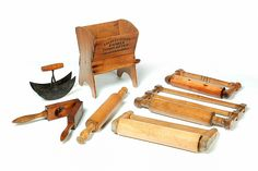 """<b>SEVEN AMERICAN WOODENWARE KITCHEN ITEMS.</b> <br /> Second half-19th century, mixed wood including maple. Four rolling pins, double bladed herb cutter and a lemon squeezer. Together with a flour sifter with hand crank and leather sifters. Labeled """"Littlefield's Family Flour Sifter, Patented June 13, 1865"""". Some splits and loss. 11""""h. Ex Elinor Meugniot."""