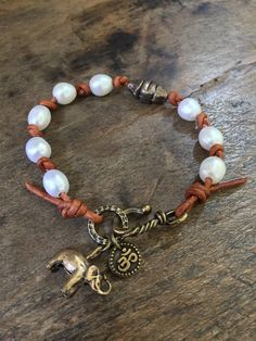 Beautiful freshwater pearls are hand knotted onto chestnut brown leather cord creating a lovely rustic-boho look. An adorable elephant and ohm charm dangle from a detailed bronze ring adding to the bohemian style.