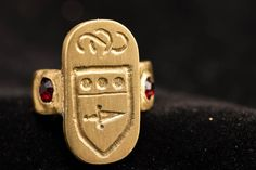 Brass and red glass signet ring. Glass is set by forming the brass over it to hold it in place. Crafted by Raven M Ridley (Cesare Amrigino di Salvazzi)