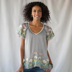 silver spring tunic  Shimmering silk flutters with each passing breeze, embroidery at the sleeves and fluttery cutaway hemline with a garden of blooms. Lace neckline.