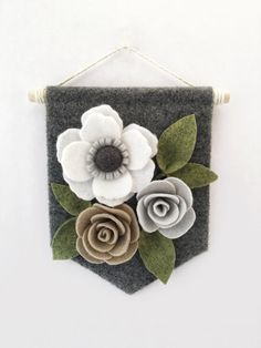 Felt Floral Banner | Made of soft and durable wool blend felt. This felt flower banner features flowers and leaves in cream, grey, taupe, green, and charcoal on a heathered charcoal felt background. The banner is made from wool blend felt wrapped around chipboard for extra stability.