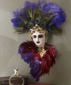 "Faux jewels and peacock plumes adorn the artistic headpiece of this mysterious enchantress. Hand-painted detail gives the ceramic mask a lifelike beauty. A beautiful collector's item, each piece is signed and numbered by the artist. A ribbon in back provides an elegant method for hanging. 14"" w x 19"" h x 6"" d.Limited Edition mask is signed and numbered by the artist!    $99.00"