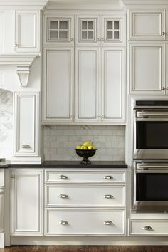 Kitchen. Cabinetry, stone countertops, and the white + stainless steel combination are lovely. Great backsplash and design.