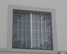 Rejas de hierro instaladas como protección de ventanas en color negro con un diseño de herrería artística.