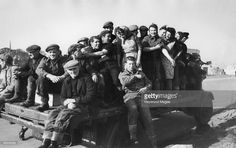 Scottish women in Great Yarmouth, Norfolk, for the herring season, are picked up by a fisherman's truck on their way to work on the quayside, December 1948. Original publication: Picture Post - 4678 - The Herring Girl Ladies - pub. 11th December 1948