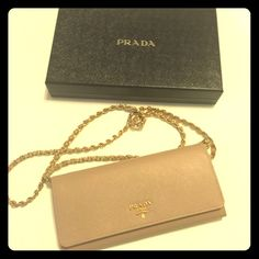 """Prada Saffiano wallet on chain, Blush (Cammeo) • Golden hardware  • Chain-leather strap; 20"""" drop • Front flap with logo detail; snap-button corners • Inside, 3 bill slots, 6 card slots, 2 open compartments, and 1 zip pocket • 4""""H x 8 1/2""""W x 1""""D • Made in Italy • Bought in Beverly Hills, CA Prada Bags Wallets"""