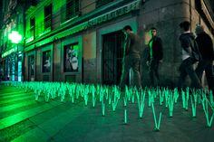 """(By the luzinterruptus): A collection of glow sticks are arranged to look like grass growing under the fluorescent lights of the abnormally bright pharmacy lights.  I love how this protest used glow sticks that appear to have """"grown"""" under the unnatural light from the sign. The artists were able to find the exact same neon color in the glow sticks as the sign."""