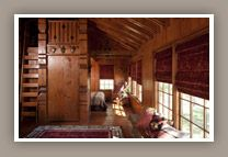 Draping roman shades in rich red velvet warms this cabin