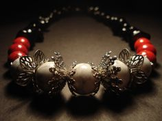 handmade necklace made of white and red chaolitis round stones, bead cups and blac stones