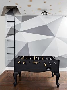 The Foosball table was painted black. The geometric mural is by Aurora Hales…
