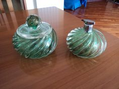 Box size: diameter 13.5 cm x height 11.5 cm; weight: 1420 gr. Perfume sprayer: diam 12.5 cm x H 10 cm; weight: 1142 gr Set of box for baby powder and perfume sprayer in Murano glass dating from the 1950s. In submerged crystal and green glass with gold leaf inclusion. Vintage items with traces of time as shown by the photos, lid chipped internally. The sprayer lacks its squeeze. Shipping via Packlink Pro.