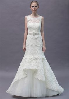 Rivini Rita Vinieris    Wysteria  $$$$$   Modified a-line of tiered French Alencon laces with a cascading peplum over a silk tulle skirt    Silhouette: A-Line  Neckline: Modest, Scoop, Sheer  Waist: Natural  Gown Length: Floor  Train Style: Attached  Train Length: Chapel  Sleeve S...