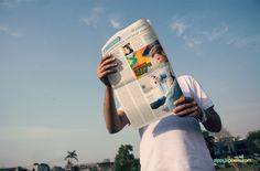 outdoor advertising mockup showing person holding newspaper from low angle with large ad and sky in background