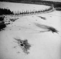 Battle Of The Bulge - Aerial view over Ardennes showing shell bursts in the snowy plantation in a clearing of the forest following Battle of the Bulge fighting. 1945