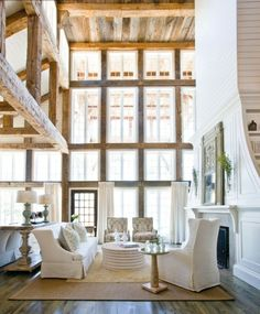 What an amazing loft space. The natural exposed wood beams add so much charm. The fireplace is exquisite, as are the huge array of windows. Such stunning composition.