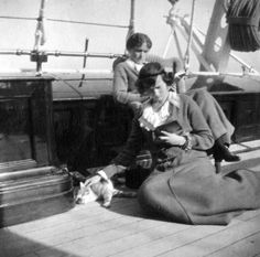Tatiana petting a cat while reading with her older sister Olga onboard the Standart. 1914