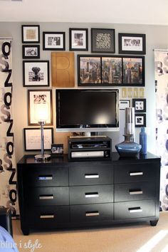 Create a gallery wall around a television to help hide it in plain sight. By choosing all black frames and black and white mats, the gallery wall maintains a sophisticated look and doesn't feel too busy.
