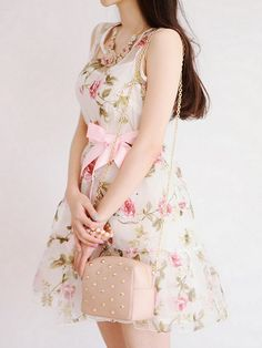 A cute floral dress with the pastel pink ribbon around the waist with the pastel…