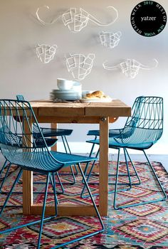 peacock blue geometric metal chairs + white wire wall sculptures + geometric bright area rug + wood table in dining room