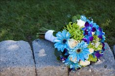 Green Spider Mums, Tinted Blue dendrobium Orchids, Blue Gerbera Daisies and White Roses make up this beautiful blue and green wedding bouquet.