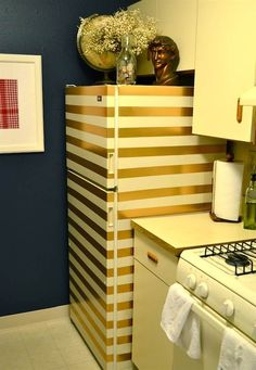 Gold & glam striped fridge tutorial. ~  #2. Go Gold:  This beautiful gold striped fridge requires only one thing — duct tape! It's inexpensive, easy to remove when the time comes and it makes a big fashion statement in an otherwise plain kitchen.