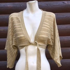 "SALE⚡️ Gold metallic cropped front tie sweater/top Fun & versatile piece to wear with a LBD or pair with jeans and a tank. Only worn a few times, it's in great condition, but if you look really close there are some spots where some threads are a tiny bit pulled. Nothing major in my opinion, and I don't believe noticeable when worn. Not absolutely perfect but still very nice.   Measures 14"" from back of the neck down, 28"" waist + ties, 17"" sleeves from shoulder. 98% acrylic 2% metallic…"