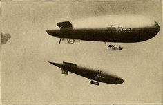 Two British Dirigibles In Flight. These are the S. S. Zero and the Parseval. The parachutecarrying case is shown attached to the envelope of the Zero.
