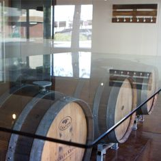 Conference room table. 500lb sheet of glass on top of 3 old wine barrels. How cool would this be as a dining room table?!?