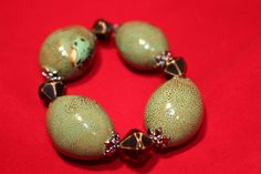 Porcelain green honey beads (36x28mm), acrylic black/gold cone shaped beads with pewter spacers.