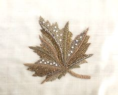 A beautiful maple leaf applique designed with Zari and zardozi in light and bright shades of gold. It is further embellished with diamantes, golden beads and bugle beads. The beauty of nature captured forever! Bead Embroidery Tutorial, Hand Embroidery Patterns Flowers, Hand Work Embroidery, Bead Embroidery Jewelry, Hand Embroidery Designs, Beaded Embroidery, Indian Embroidery, Zardosi Embroidery, Couture Embroidery