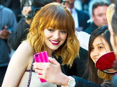 Emma Stone shows off her brand new bangs as she takes a selfie with a fan at The Amazing Spider-Man 2 premiere Thursday at the Ziegfeld Theater in New York City.
