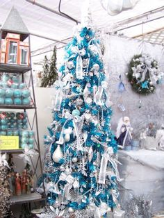 Blue Christmas tree decorated in white.